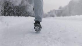 Siluetta di un funzionamento dell'uomo lungo una strada nevosa nell'inverno in un parco stock footage