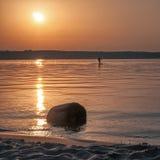 Siluetta di un funzionamento dell'uomo sull'acqua a sunse Fotografia Stock