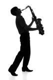 Siluetta di un giovane che gioca uno strumento di vento su fondo isolato Fotografie Stock