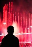 Siluetta di un giovane che guarda alle fontane musicali illuminate variopinte nella sera Immagine Stock Libera da Diritti