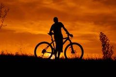 Siluetta di un giovane con una bicicletta al tramonto fotografia stock