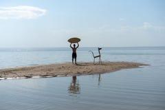 Siluetta di un giovane con uno skimboard sulla spiaggia immagine stock