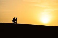 Siluetta di un gruppo di persone che camminano durante l'alba Fotografia Stock Libera da Diritti