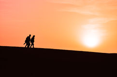 Siluetta di un gruppo di persone che camminano in Sahara Desert Fotografie Stock