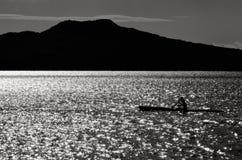 Siluetta di un kayak del mare dell'uomo Fotografie Stock