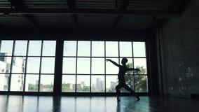 Siluetta di un maschio del ballerino di balletto contro lo sfondo di grande finestra Movimento lento archivi video