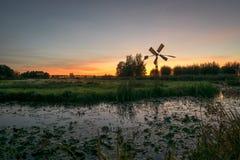 Siluetta di un mulino di pompaggio olandese e degli alberi con i colori crepuscolari subito dopo il tramonto immagini stock libere da diritti