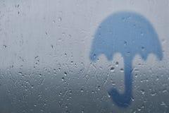 Siluetta di un ombrello su un fondo di vetro con le gocce e le gocce di pioggia immagine stock libera da diritti