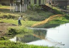 Siluetta di un pescatore che getta un a rete in un lago Fotografie Stock