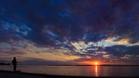 Siluetta di un pescatore che sta su un paesaggio del fondo di tramonto Fotografie Stock