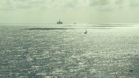 Siluetta di un petrolio Rig Drilling Platform e delle navi Oceano Atlantico mezzogiorno stock footage
