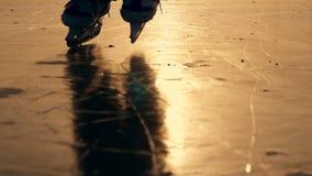 Siluetta di un ragazzo che pattina sul ghiaccio su un lago nell'inverno al sole Movimento lento stock footage