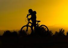 Siluetta di un ragazzo su una bicicletta al tramonto Fotografia Stock Libera da Diritti