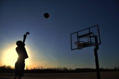 Siluetta di un ragazzo teenager che spara una pallacanestro Fotografia Stock