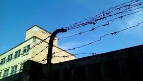 Siluetta di un recinto concreto con filo spinato fotografie stock