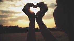 Siluetta di un simbolo del cuore dalle mani di una giovane donna in un campo su un fondo di tramonto video d archivio