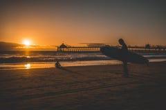 Siluetta di un surfista su una spiaggia sabbiosa con il tramonto sui precedenti immagini stock