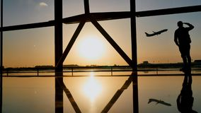 Siluetta di un tipo turistico che guarda il decollo dell'aereo che sta alla finestra dell'aeroporto al tramonto nella sera immagine stock