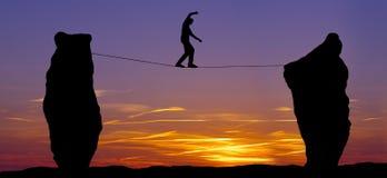 Siluetta di un uomo che cammina sulla corda per funamboli Fotografia Stock Libera da Diritti