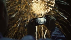 Siluetta di un uomo che fotografa i fuochi d'artificio al cielo notturno Bello saluto in onore della festa stock footage
