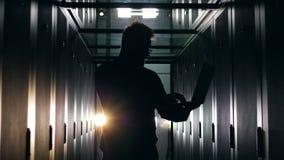 Siluetta di un uomo che lavora ad un computer portatile in una stanza del server Concetto della stanza del server di centro dati archivi video