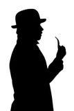 Siluetta di un uomo in un cappello con un tubo. fotografia stock libera da diritti