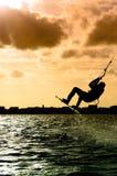Siluetta di un volo del kitesurfer immagine stock libera da diritti