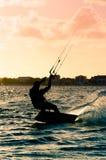 Siluetta di un volo del kitesurfer immagine stock