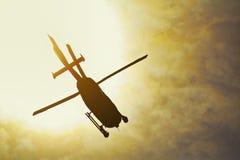 Siluetta di un volo dell'elicottero nei raggi del tramonto Fotografia Stock Libera da Diritti