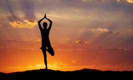 Siluetta di un'yoga della donna nella sera Fotografia Stock
