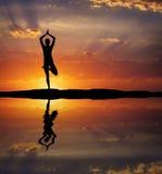 Siluetta di un'yoga della donna nella sera Donna che fa yoga alla s Fotografia Stock