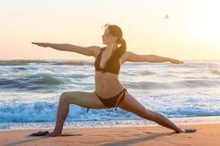 Siluetta di un'yoga di pratica della giovane donna sulla spiaggia ad alba Sport, concetto di benessere Fotografie Stock Libere da Diritti