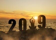 Siluetta di un'yoga di pratica della ragazza durante il nuovo anno 2019 di celebrazione fotografia stock