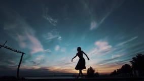Siluetta di una ballerina che balla contro il cielo di tramonto ragazza che balla e che fila sulla punta dei piedi video d archivio