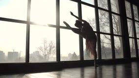 Siluetta di una ballerina sui precedenti di grande finestra Ballerino di balletto che fa allungamento archivi video