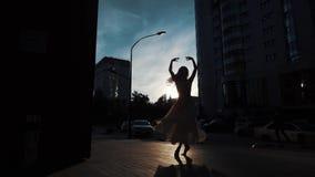 Siluetta di una ballerina in un vestito volante che balla all'aperto ragazza esile che balla sui precedenti delle costruzioni urb video d archivio