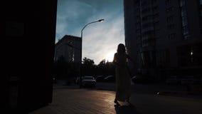 Siluetta di una ballerina in un vestito volante che balla all'aperto ragazza esile che balla sui precedenti delle costruzioni urb archivi video