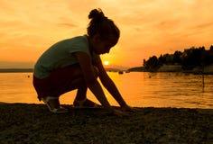 Siluetta di una bambina alla spiaggia Fotografia Stock Libera da Diritti