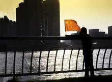 Siluetta di una bandiera d'ondeggiamento del cinese del giovane ragazzo Fotografie Stock Libere da Diritti