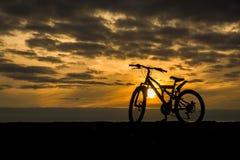 Siluetta di una bicicletta contro il tramonto Immagini Stock Libere da Diritti