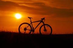 Siluetta di una bicicletta sul fondo di tramonto fotografia stock libera da diritti