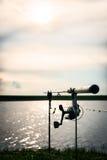 Siluetta di una canna da pesca con il fuoco sulla bobina Fotografia Stock Libera da Diritti