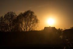 Siluetta di una casa e degli alberi vicino alla strada vuota con polvere in cou fotografie stock libere da diritti