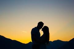 Siluetta di una coppia della persona appena sposata sui precedenti del tramonto Fotografie Stock Libere da Diritti