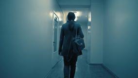Siluetta di una donna che cammina giù un corridoio scuro verso la fine della sera stock footage