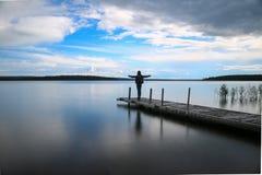 Siluetta di una donna che cammina su un pilastro nel lago Fotografia Stock