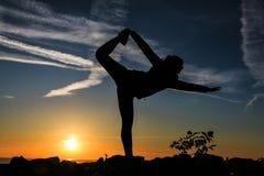 Siluetta di una donna che fa figura relativa alla ginnastica fotografia stock libera da diritti
