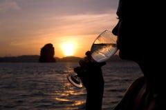 Siluetta di una donna che mangia vino durante il tramonto Immagine Stock Libera da Diritti