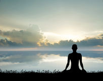 Siluetta di una donna che medita su tramonto Fotografia Stock Libera da Diritti