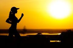 Siluetta di una donna che pareggia sulla natura al tramonto, al profilo della ragazza di sport, al concetto dello sport ed allo s Fotografie Stock Libere da Diritti